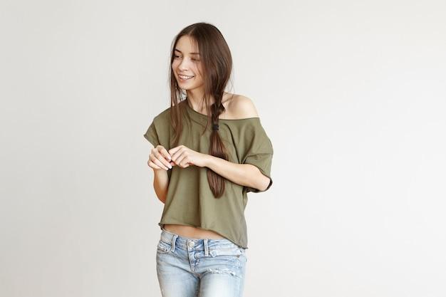 ジーンズを身に着けている乱雑な髪型とオープンショルダーのトップで遊び心のある美しい10代の少女 無料写真