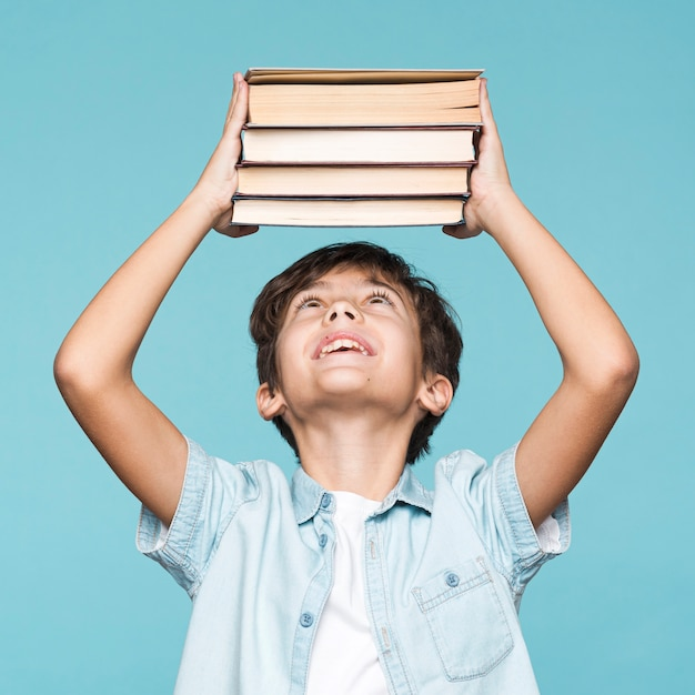 Playful boy holding stack of books Free Photo