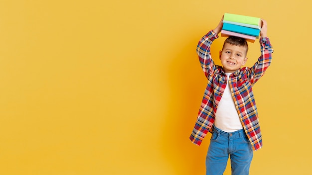 Playful boy with stack of books on his head Free Photo
