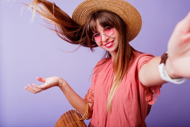 Игривая брюнетка женщина в соломенной шляпе и розовые очки, делая автопортрет над бархатом. ношение элегантного платья. Бесплатные Фотографии