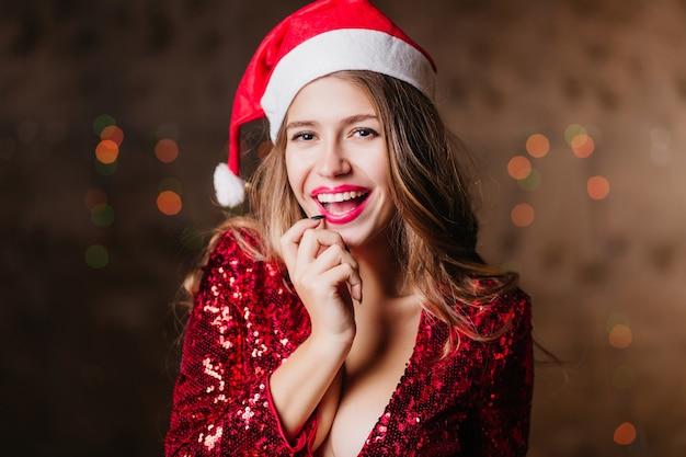 Игривая брюнетка с темными глазами позирует в шляпе санта-клауса с красивой улыбкой на блестящей стене Бесплатные Фотографии