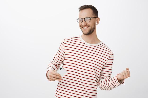 Игривый беззаботный кавказский парень с щетиной в модных черных очках, закрывает глаза и радостно улыбается, имитируя игру на невидимой гитаре Бесплатные Фотографии