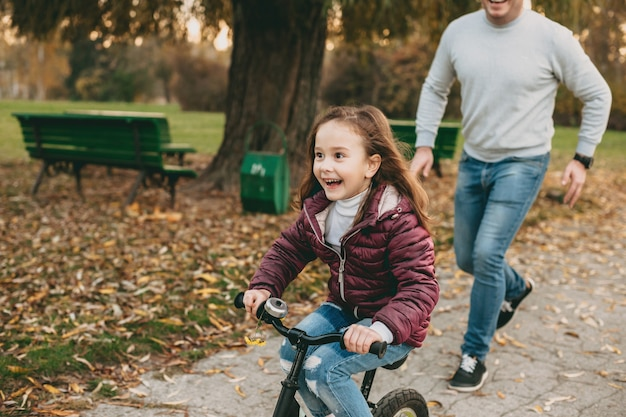 彼女が幸せに自転車に乗っている間、公園で彼の娘と一緒に歩いている遊び心のある白人の父親 Premium写真