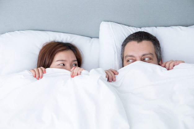 Playful couple hiding behind blanket in bed Free Photo
