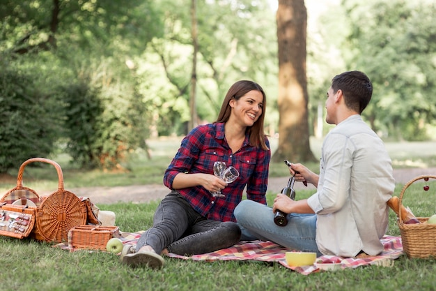 Playful couple lying on a blanket with wine glasses Free Photo