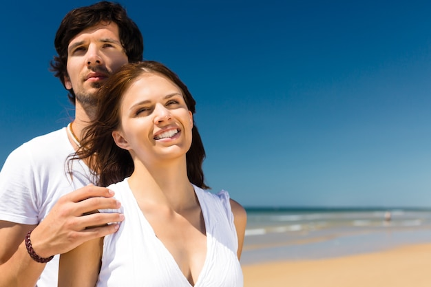 Playful couple on the ocean beach enjoying their summer vacation, he embraces her Premium Photo