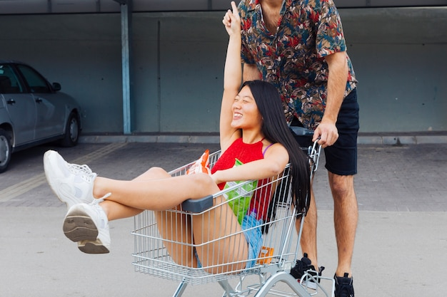 Playful couple riding in shopping trolley Free Photo