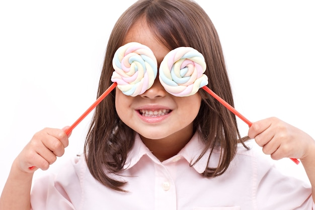 Playful cute little girl posing with sweet pastel color marshmallow Premium Photo