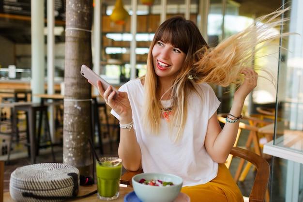 Игривая девушка, наслаждаясь вкусным завтраком во время праздников в стильном современном кафе. Бесплатные Фотографии
