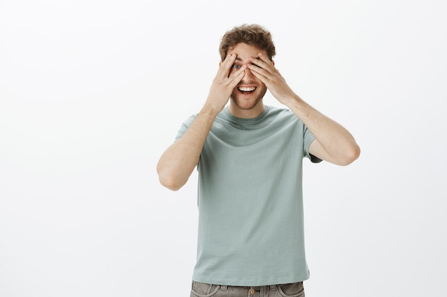 Playful happy man model in t-shirt, covering eyes with palms and peeking through fingers, smiling broadly Free Photo