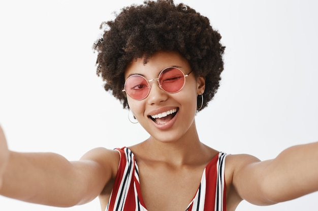 Playful hot african american with afro hairstyle, pulling hands towards to make selfie, winking joyfully and smiling broadly, making new profile pic for social network Free Photo