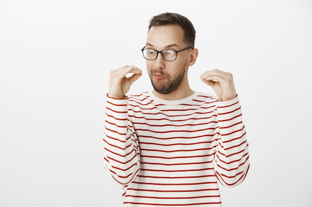 Playful insane adult guy in black glasses, talking with hands Free Photo