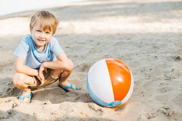 Playful kid sitting next to wind ball Free Photo