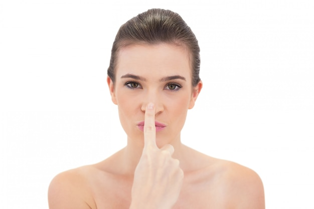 Playful natural brown haired model touching her nose Premium Photo