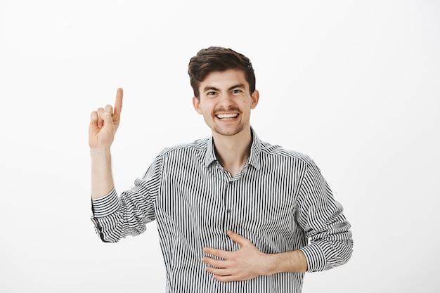 Игривый позитивный друг-мужчина с усами и родинками на лице, поднимающий указательный палец, держащий руку на животе, громко смеющийся, вспоминая забавный момент во время вечеринки над серой стеной Бесплатные Фотографии