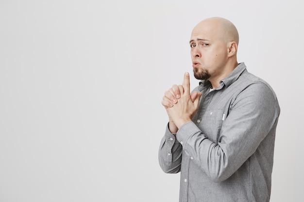 Игривый нахальный взрослый лысый парень показывает жест пистолета, подражая секретному агенту Бесплатные Фотографии