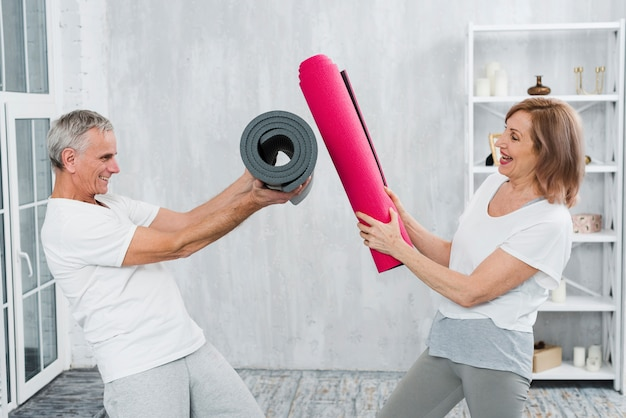 Playful senior couple fighting with yoga mat roll Free Photo