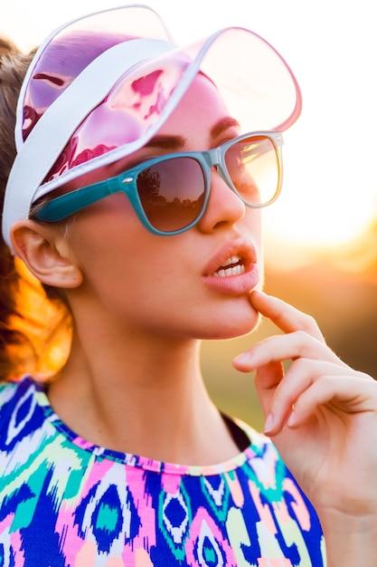Ragazza esile giocosa in elegante crop top colorato, cappuccio trasparente e occhiali da sole in posa sulla strada al tramonto. Foto Gratuite