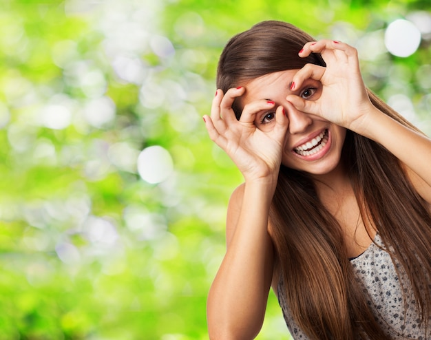 Playful teenager showing glasses gesture Free Photo