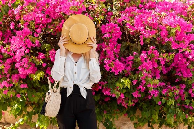 Игривая женщина прячется за соломенной шляпе Бесплатные Фотографии