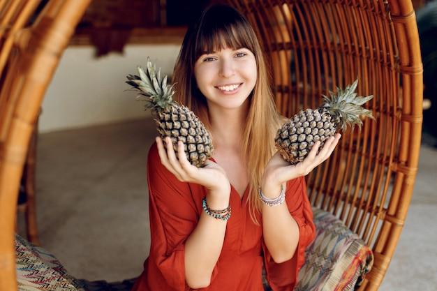 Donna allegra che tiene due ananas, seduto sulla sedia di bambù appesa Foto Gratuite