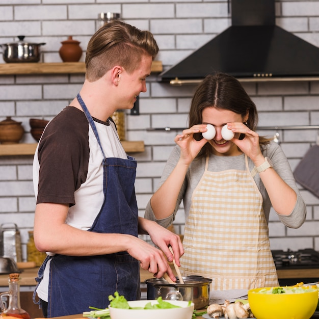 Playful woman with man cooking in kitchen Free Photo