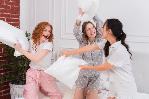 Playful women fighting with pillows Free Photo