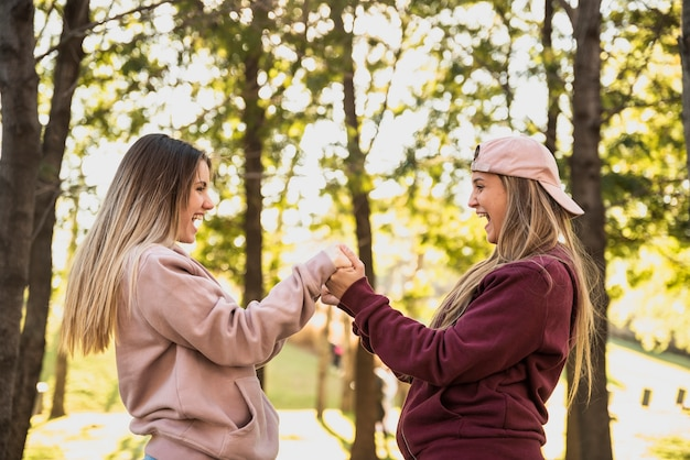 Playful women holding each other hands Free Photo
