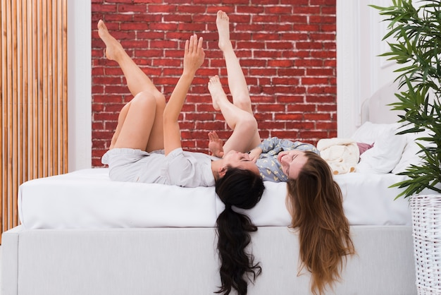 Playful women laid in bed with legs up Free Photo
