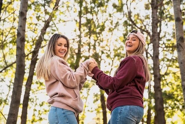 Playful women looking at camera holding hands Free Photo