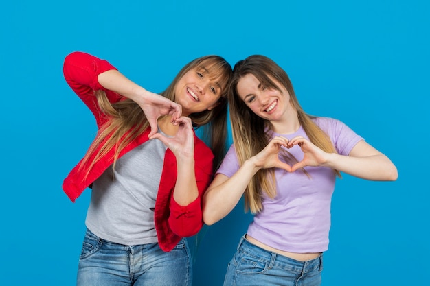 Playful women with hands in heart shape Free Photo