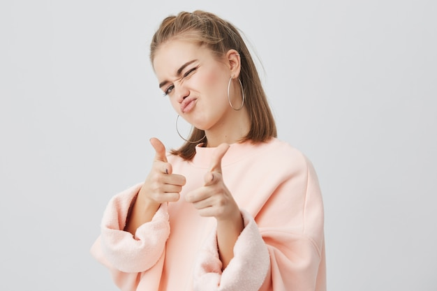 Игривая молодая кавказская женщина с прямыми светлыми волосами, одетая в розовую толстовку с длинными рукавами, стоит, издевается, указывая указательными пальцами на тебя Бесплатные Фотографии