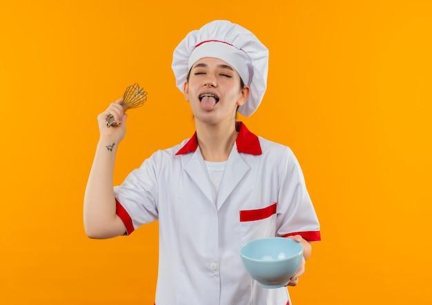 オレンジ色のスペースで隔離された目を閉じて舌を示す泡立て器とボウルを保持しているシェフの制服を着た遊び心のある若いかわいい料理人 無料写真