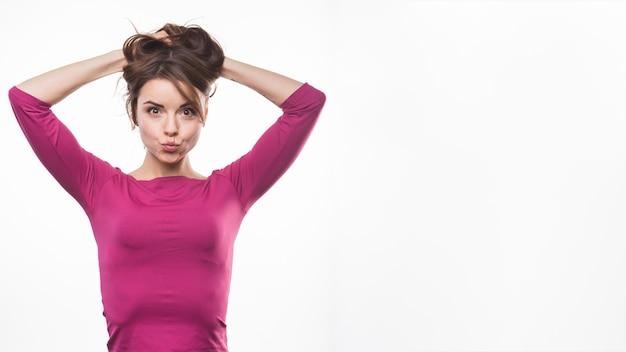 Giovane donna allegra che fa il broncio con le sue mani in testa Foto Gratuite