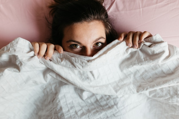 Playful young woman with beautiful eyes hiding face under blanket while lying in cozy bed Premium Photo