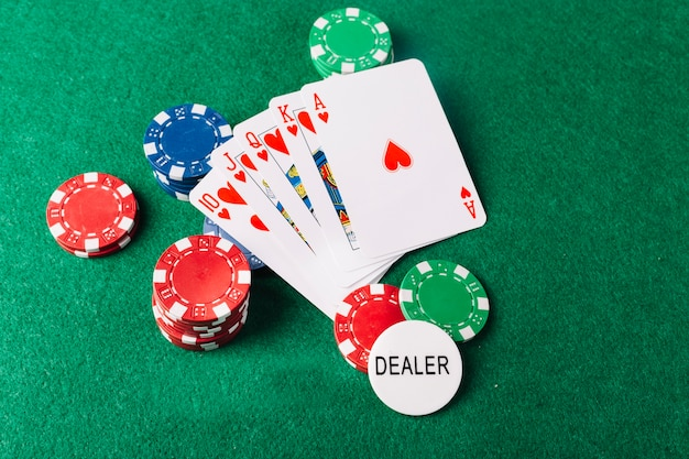 Playing cards and casino chips on green surface Free Photo