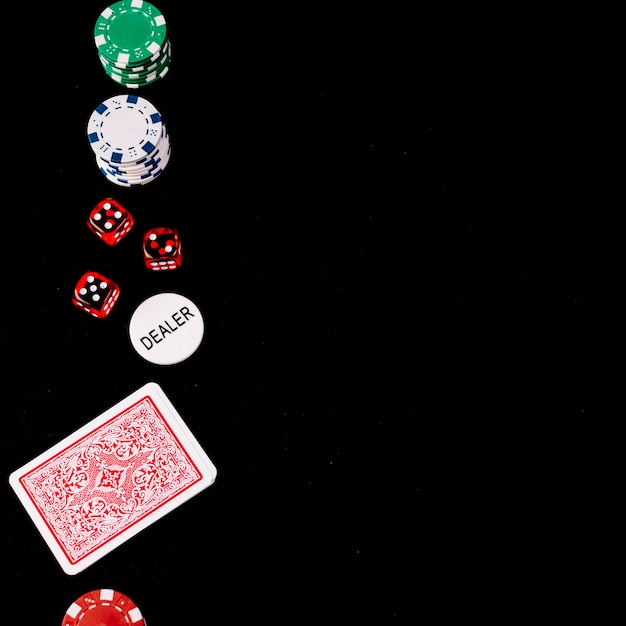 Playing cards; dice; poker and dealer chips on black backdrop Free Photo