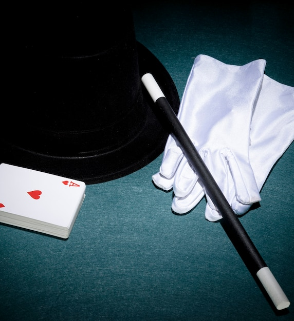 Playing cards; white gloves; top hat and magic wand on green background Free Photo