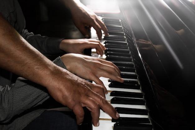 Играет четыре мужские руки на пианино. ладони лежат на клавишах и играют на клавишном инструменте в музыкальной школе. студент учится играть. руки пианиста. черный темный фон. Premium Фотографии