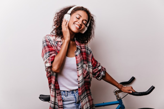 Pleasant black girl enjoying music with eyes closed. appealing african lady listening favorite song during shotshoot with bicycle. Free Photo