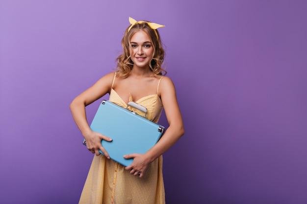 青いスーツケースを持った心地よい日焼けした女性。紫の荷物でポーズをとる黄色いリボンの楽観的な女性モデル。 無料写真