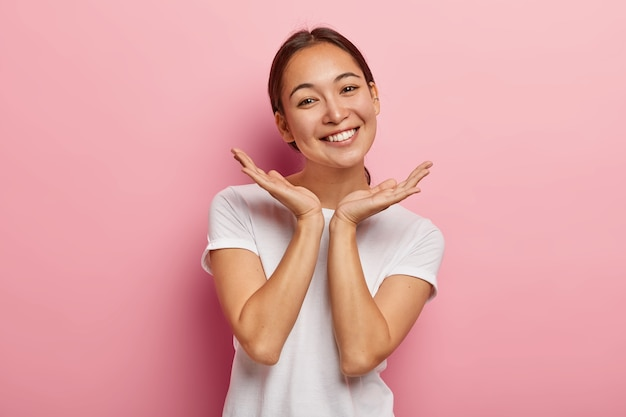Pleasant looking asian female model smiles gladfully, spreads palms near face, expresses positive emotions, wears white t shirt, has appealing appearance, healthy skin, isolated on pink  wall Free Photo