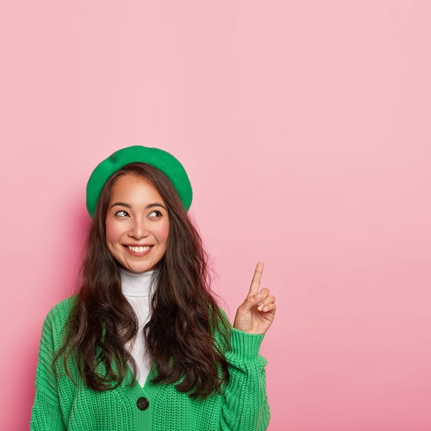Pleasant looking asian lady wears green beret and knitted jumper, points fore finger above, has cheerful expression Free Photo