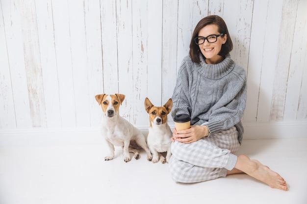 カジュアルな服装の快適なブルネットの女性、紙コップから熱い飲み物を飲む、2匹の犬の近くに座っています。 Premium写真