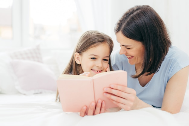 Pleasant looking female child with curious expression, reads interesting book together with her affectionate mother Premium Photo