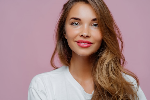 Pleasant looking female model has tender smile, wears minimal makeup, has long wavy hair, looks at camera Premium Photo