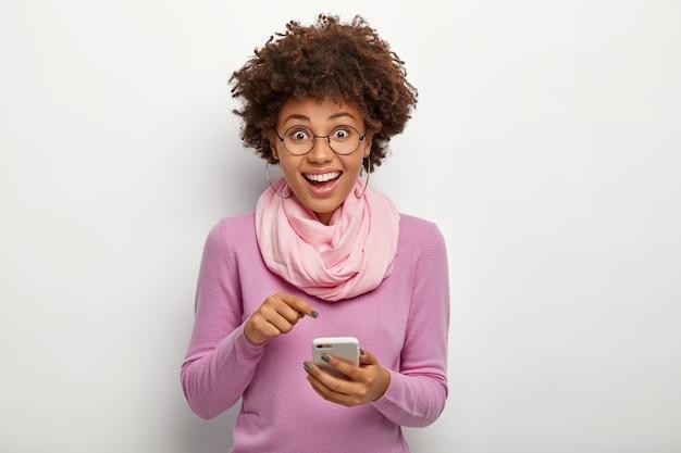 선명한 머리카락을 가진 유쾌한 여성, 휴대 전화 장치를 가리키고, 새로운 현대 응용 프로그램을 장착하고, 행복한 표정을 지으며, 시력 교정을 위해 안경을 쓰고, 보라색 점퍼와 실크 스카프를 착용합니다. 무료 사진
