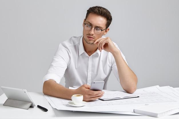 유쾌한 남성 건축가는 태블릿 컴퓨터를 진지하게 들여다보고 메모와 스케치로 작업하고 커피를 마시 며 매우 바쁩니다. 재능있는 젊은 남성 엔지니어가 건설 프로젝트에서 일합니다. 무료 사진