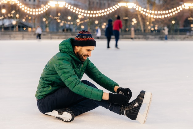 Pleasant looking man wears green coat and hat, sits on ice and laces up skates, going to skate Premium Photo