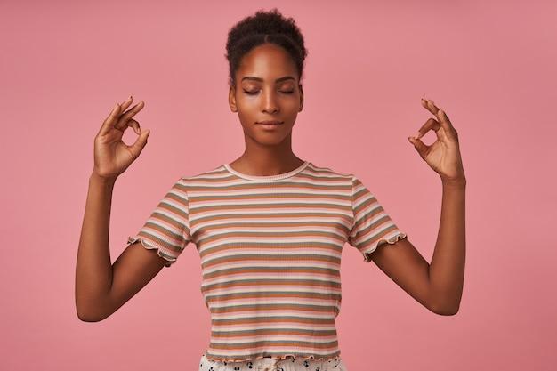 ピンクの壁に隔離された目を閉じて瞑想しながらムードラジェスチャーで手を上げる快適に見える若い茶色の髪の巻き毛の女性 無料写真